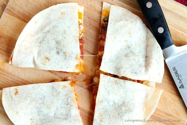 Cut chicken fajita quesadilla in quarters