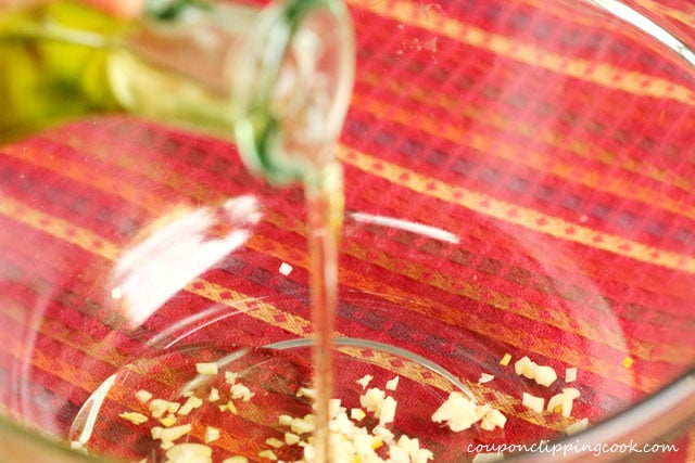 Pour olive oil in bowl with garlic