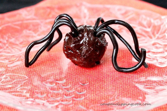 Candy spider legs on rolled chocolate truffle on plate