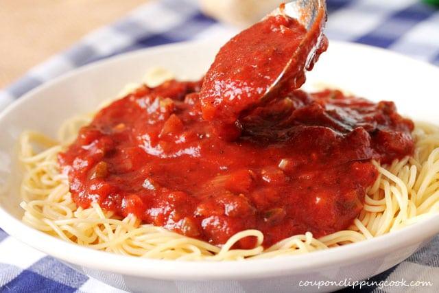 Add marinara sauce on top of spaghetti in bowl