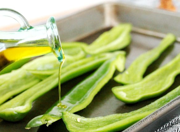 Drizzle olive oil on sliced green chiles in pan