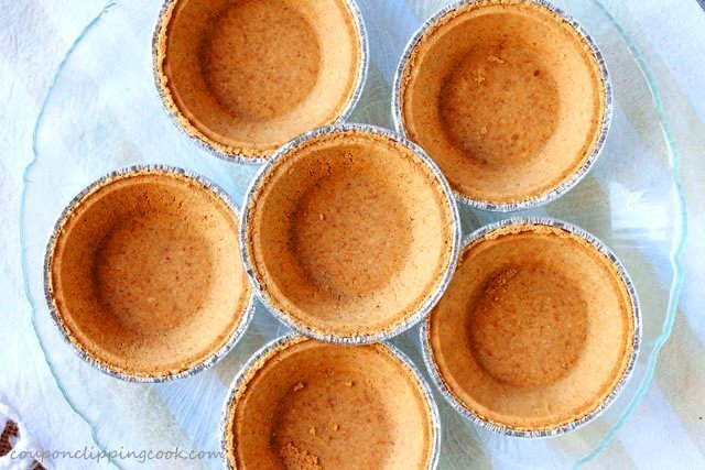 Premade mini graham cracker pie crusts on plate