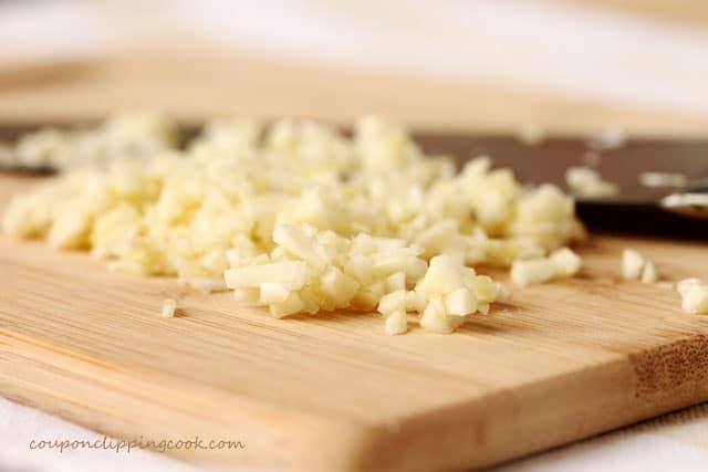 Chop garlic on cutting board with knife