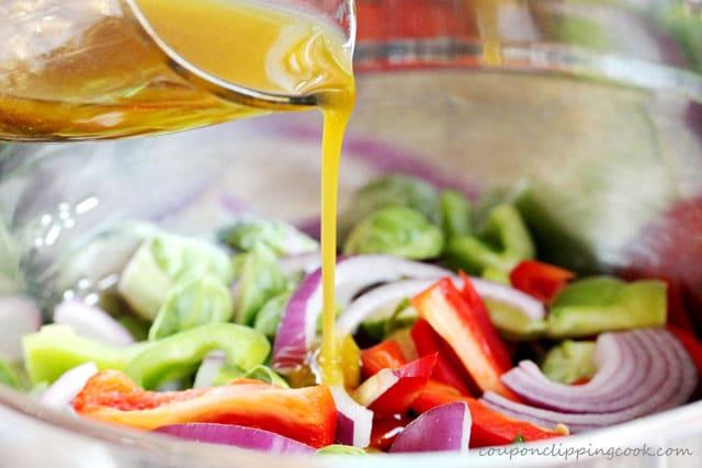 Add fajita marinade to vegetables in mixing bowl