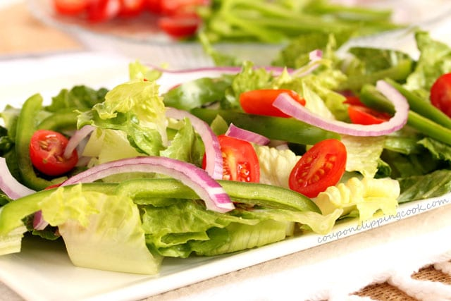 Salad with lettuce, red onion, green bell pepper and tomatoes on plate