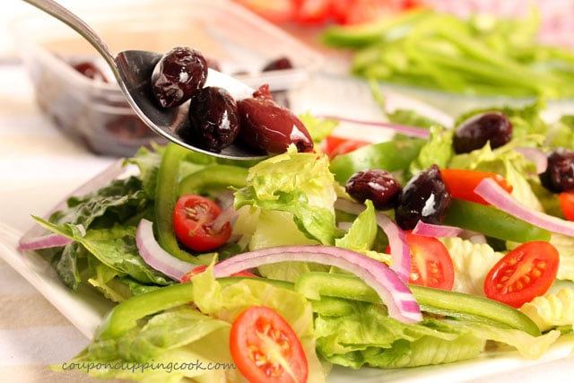 Add kalamata olives on salad on plate