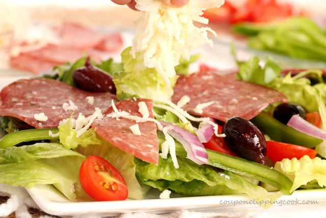 Add shredded mozzarella cheese on Antipasto salad on plate