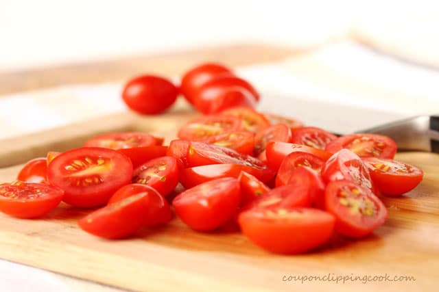 Cut cherry tomatoes on cutting board