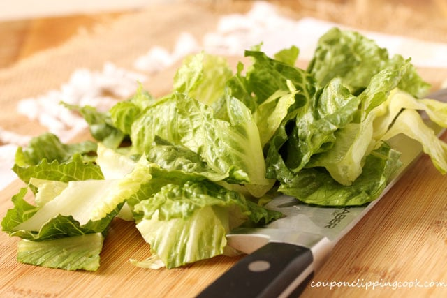 Cut pieces of Romaine lettuce on cutting board with knife