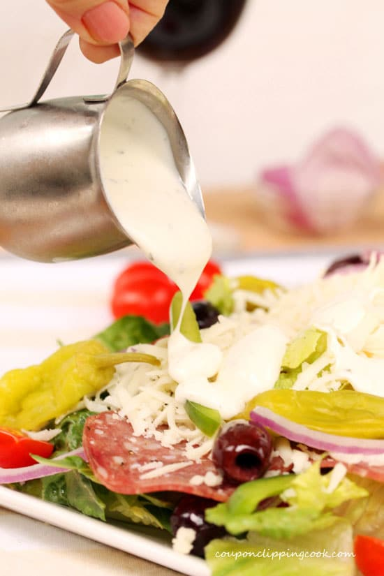 Pour Caesar Dressing on Antipasto Salad with Olives and Salami