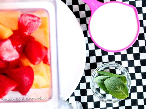 Fruit in blender by mint leaves and coconut milk
