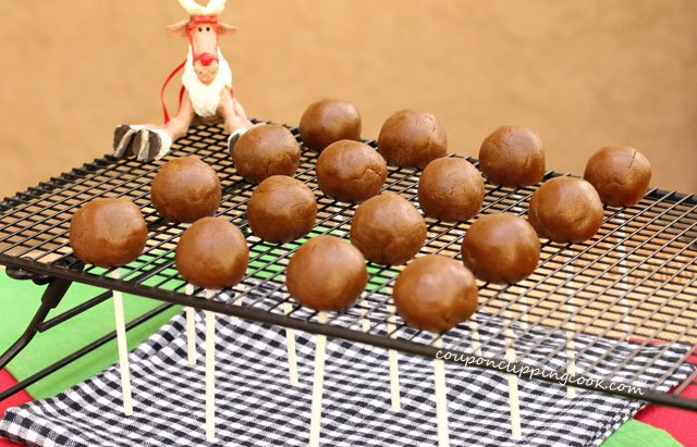 Rolled gingerbread cookie dough balls with stick on rack