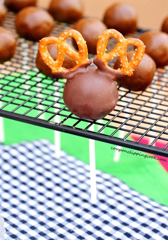 Mini pretzels attached to cookie dough ball with chocolate on rack
