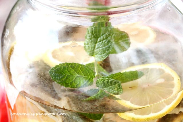 Spring of mint in jar with green tea and lemon