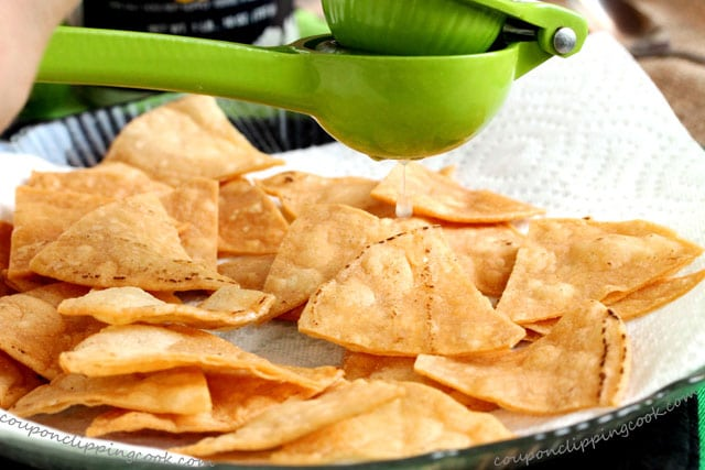 Squeeze lime juice on tortilla chips on plate