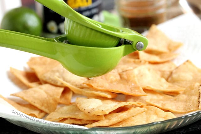 Squeeze lime juice on tortillas chips on plate
