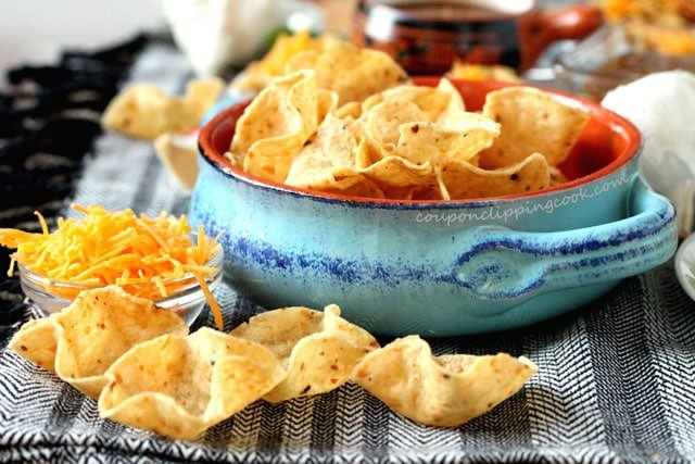 Tortilla chips in bowl with shredded cheese
