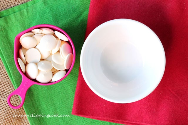 White candy coating discs in measuring cup with bowl