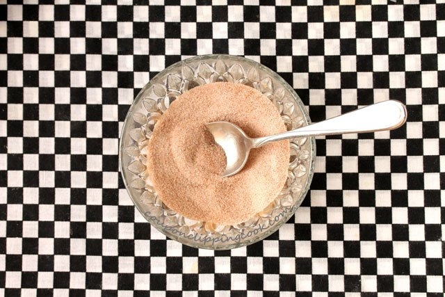 Ground cinnamon and sugar in bowl with spoon