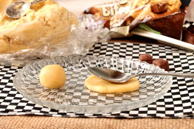 Flatten cookie dough ball on plate with spoon