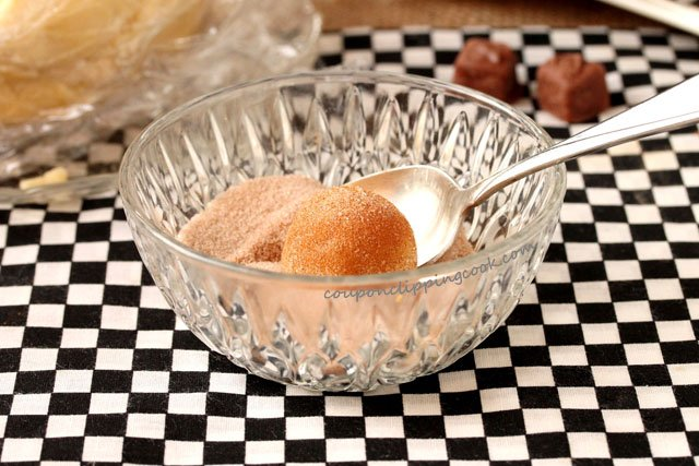 Coat cookie dough ball with cinnamon and sugar in bowl