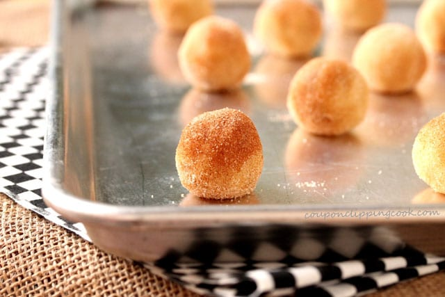 Cookie dough balls coated with cinnamon and sugar on cookie pan
