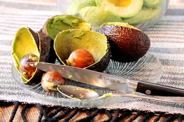 Avocado skins and seeds on plate with knife