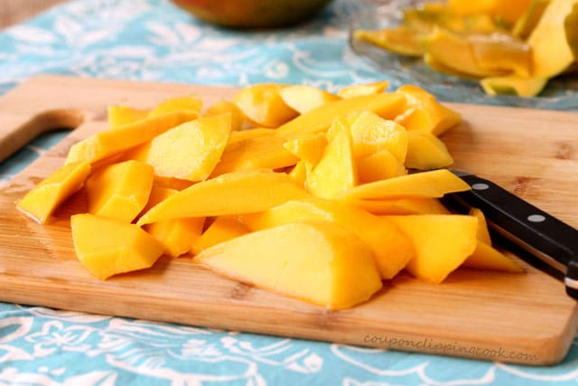Cut mangos on cutting board with knife