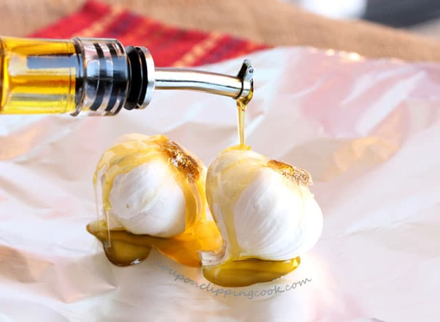 Drizzle olive oil on bulbs of garlic on foil