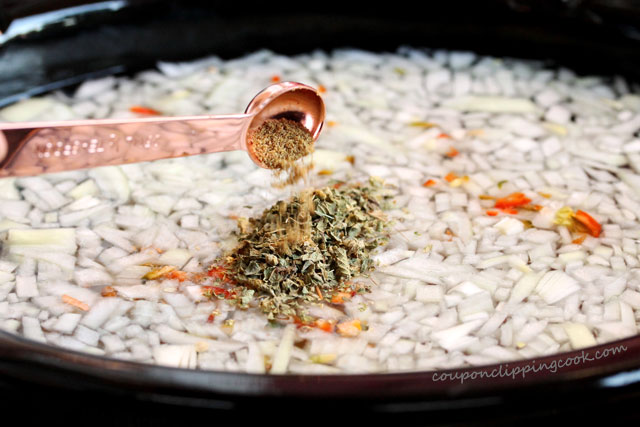 Add ground cumin to pot with onions and pinto beans