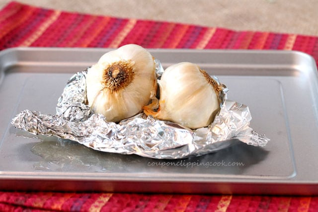 Roasted bulbs of garlic in foil on pan