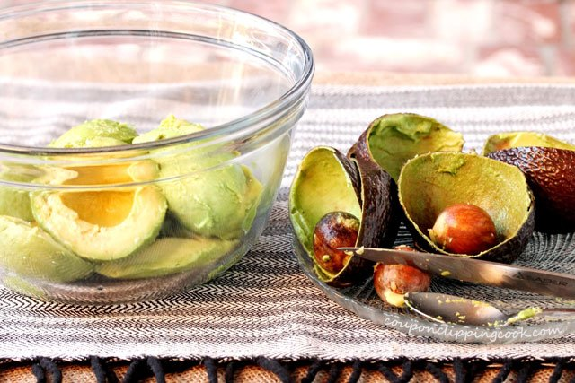 Avocado meat in bowl with avocado skins and seeds on plate