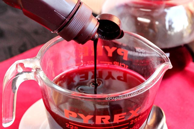 Pour chocolate syrup in cup with pomegranate juice