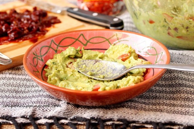 Layer guacamole in bowl with spoon