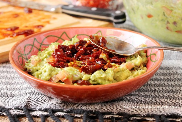 Layered Chipotle Guacamole in bowl with spoon