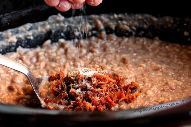 Add salt to Slow Cooker Roasted Garlic Pinto Bean Mash in pot