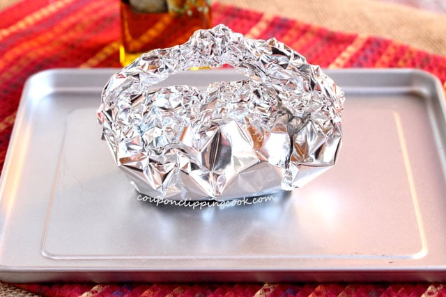Foil tent with bulbs of garlic inside on pan
