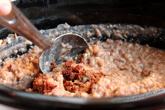 Stir Slow Cooker Roasted Garlic Pinto Bean Mash with spoon
