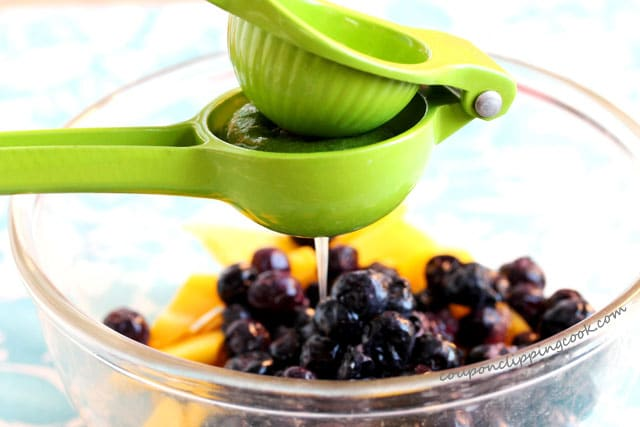 Squeeze lime juice in bowl with blueberries and mangos