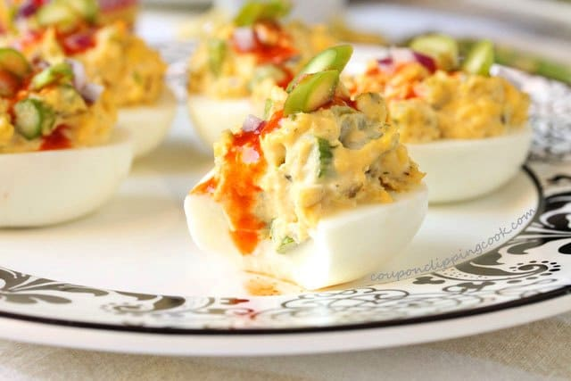 Bite of Spicy Deviled Eggs with Asparagus on plate