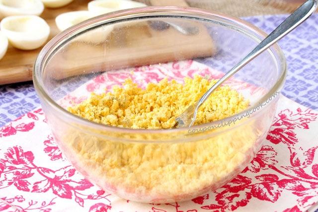 Mash hard boiled egg yolks in bowl with fork