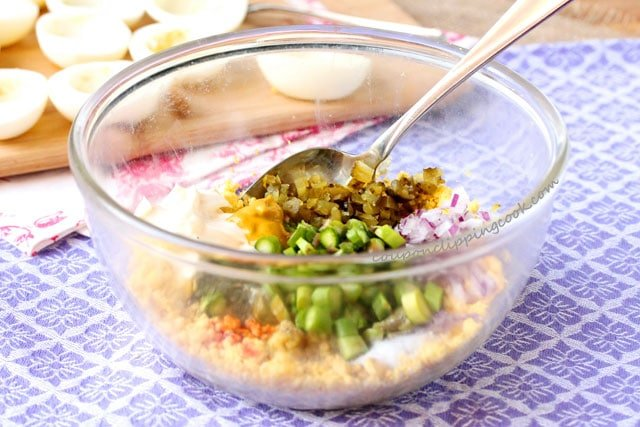 Mashed egg yolks, mayonnaise, mustard, onion and pickle in bowl