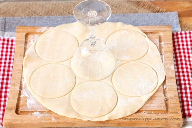 Cut pie dough with glass on cutting board