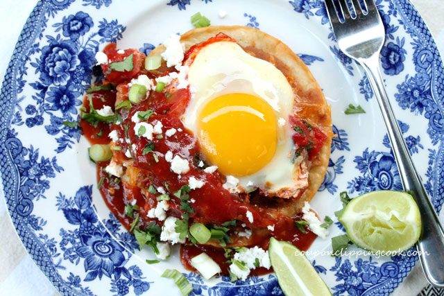 Huevos Rancheros (egg tostadas) on plate with fork