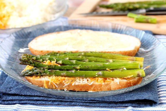 Lay asparagus over cheese on slice of bread on plate