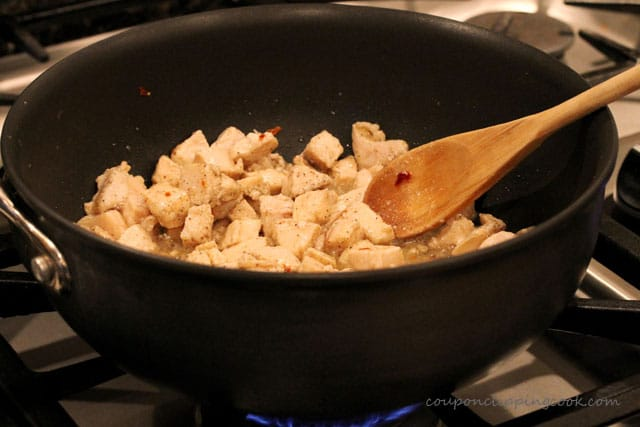 Cook cut pieces of chicken in pan