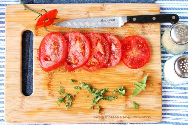 Sliced tomatoes and herbs on cutting board with knife