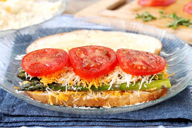 Sliced tomatoes, cheese and asparagus on slice of bread on plate