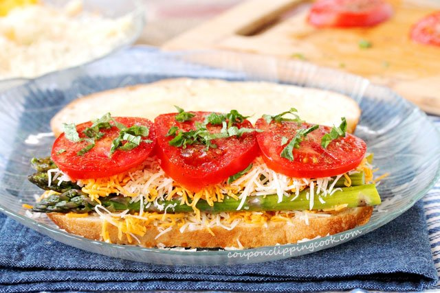 Herbs, tomatoes cheese and asparagus on slice of bread on plate