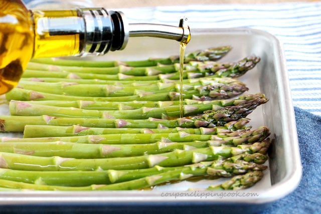 Drizzle olive oil on asparagus spears in baking pan